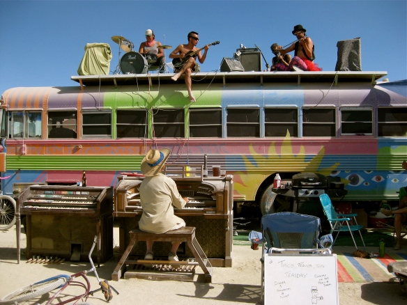 Man playing the piano, fellow musicians sit on the top of a bus nearby.